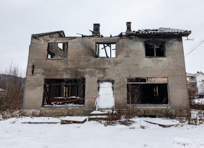 Lyngdal Norge - januari 2018: Bruten bränd konkret byggnad i vinter, snö på jordningen norway fotografering för bildbyråer