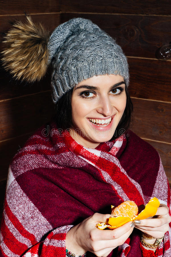 Lynnet av vintern Ung härlig brunett som ler i kläder och lock med tangerin på träbakgrund arkivbilder