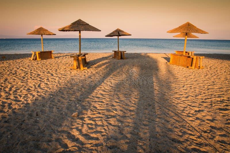 Lynnig fridsam strand- och havssikt med parasoller på toningen för splittring för solnedgångchilloutfärg arkivbilder