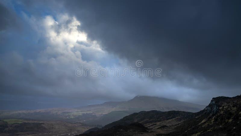 Lynnig och dramatisk vinterlandskapbild av Moel Saibod från Crimpiau i Snowdonia med att bedöva axlar av ljus i stormigt arkivbild