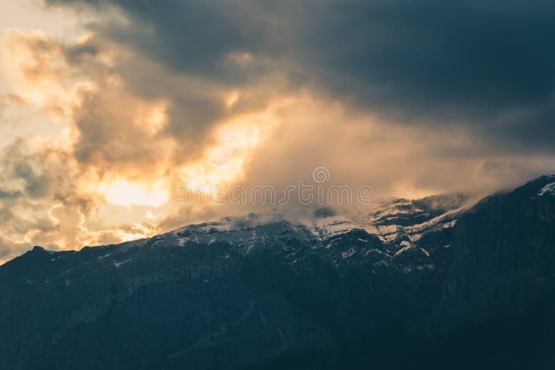 Lynniga moln på solnedgången ovanför steniga berg royaltyfria foton
