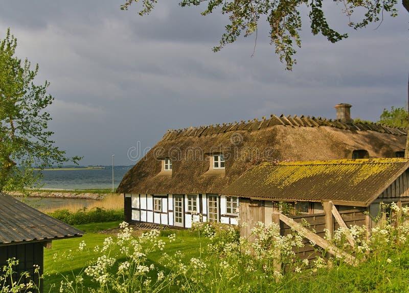 Lyo Danmark - Juli 4th, 2012 - traditionellt timmer-inramat halmtäckt danskt lantbrukarhem på ön av Lyo i det baltiskt royaltyfria bilder