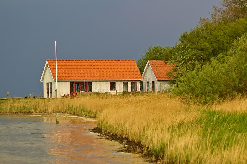 Lyo, Denmark - May 28th, 2011 - White clapboard house with red tile roof housing the marina facilities on the reed-covered shore o. F the island of Lyo in the royalty free stock image
