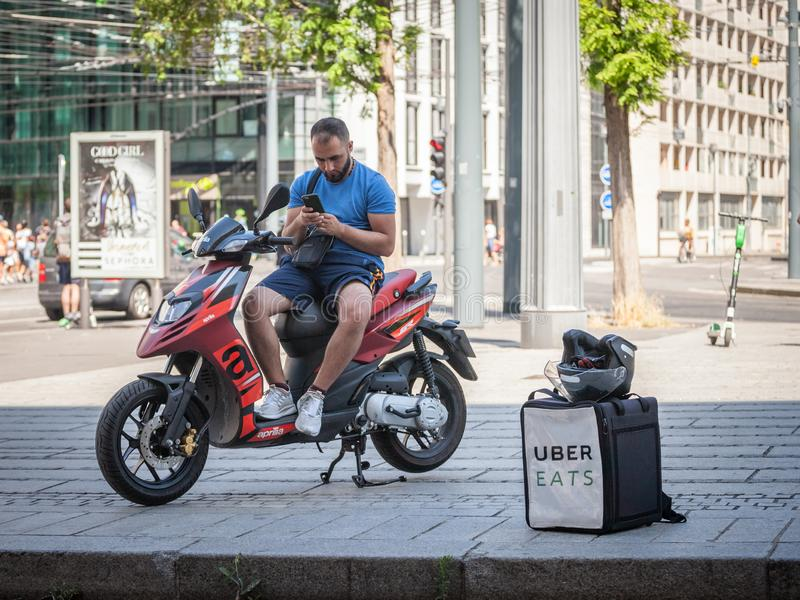 Uber Eats logo on the bag of a delivery man on his scooter, using his smartphone to wait for the next food order from a restaurant stock photography