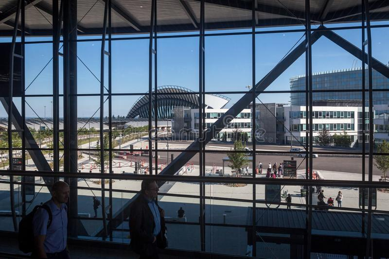 Passengers passing by the terminal 1 of Aeroport de Lyon Airport, Saint Exupery, while the iconic train station of the airport. LYON, FRANCE - JULY 13, 2019 stock photo