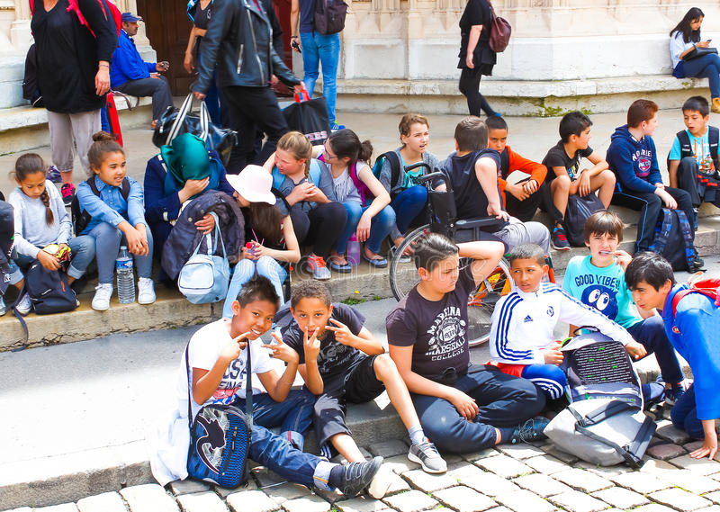 Lyon, France - June 16, 2016: group of children sitting on the steps the cathedral in the old town royalty free stock photo