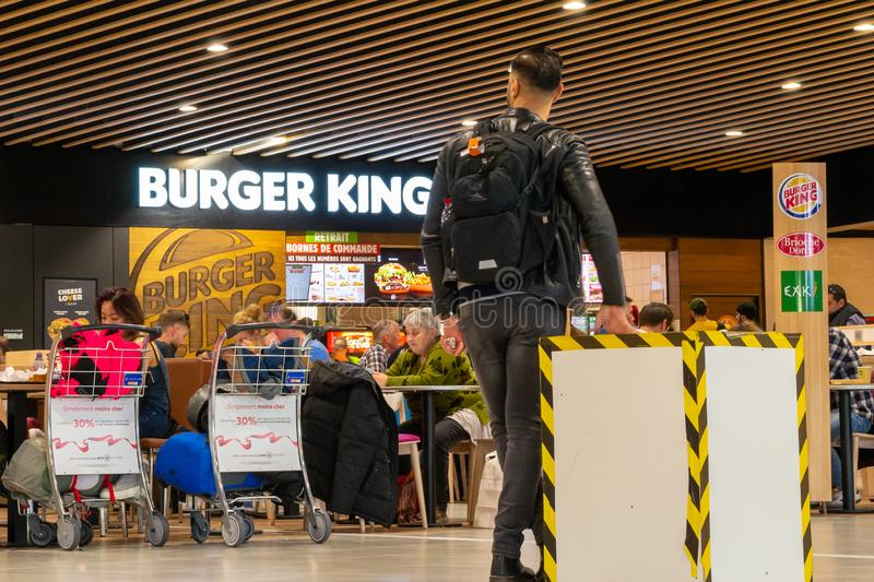 Man looking towards the Burger King food area in Lyon-Saint Exupery Airport, while waiting for his flight. Lyon, France - 16 March 2019: Man looking towards the stock photo