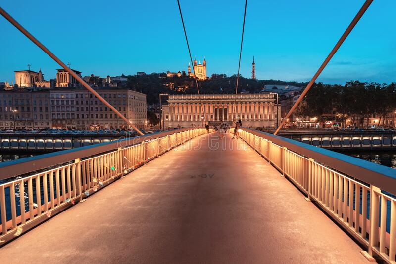 Lyon night cityscape with illuminated Courthouse and red pedestrian bridge over Saone river. Panoramic stock photos