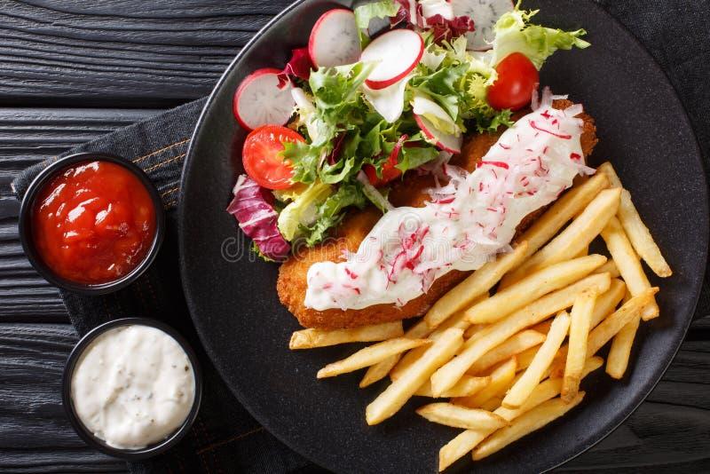 Lyrtorsk i br?dsmulor som garneras med pommes frites och den nya salladcloseupen horisontalb?sta sikt arkivbilder