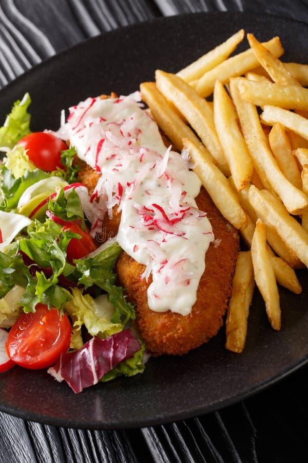 Lyrtorsk i br?dsmulor som garneras med pommes frites och den nya salladcloseupen vertikalt royaltyfri bild