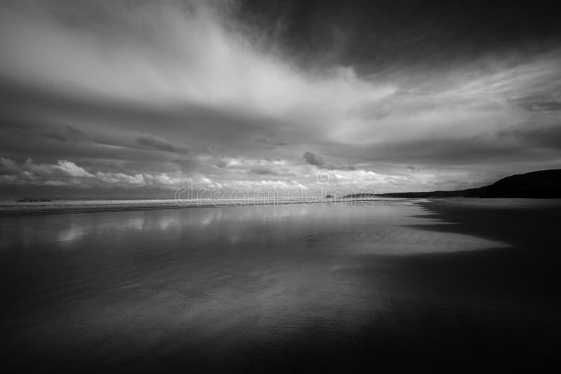 Lysande moln och silhouetted udde på den öde stranden, Perr arkivbild