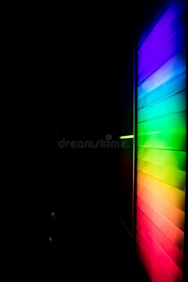 lysande spektrum som komponeras av prismor och projekteras på en väggintelligens royaltyfri bild