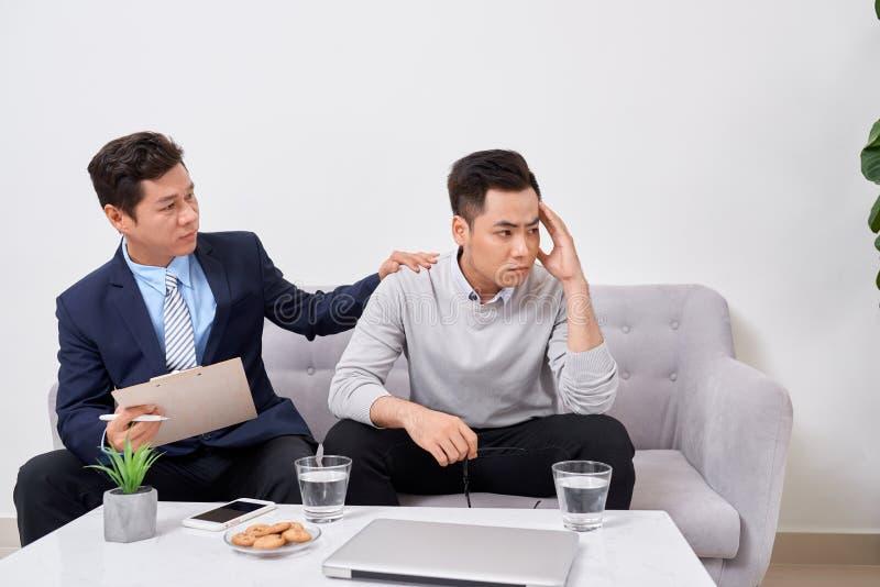 Lyssna till mig Asiatisk man som rynkar pannan, medan se hans terapeut fotografering för bildbyråer