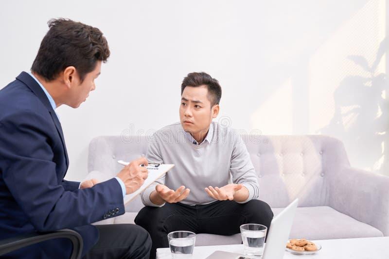 Lyssna till mig Asiatisk man som rynkar pannan, medan se hans terapeut royaltyfri bild