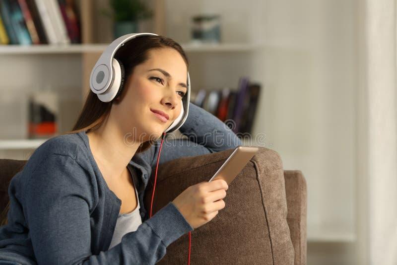 Lyssnande chilloutmusik för avkopplad kvinna hemma arkivbilder