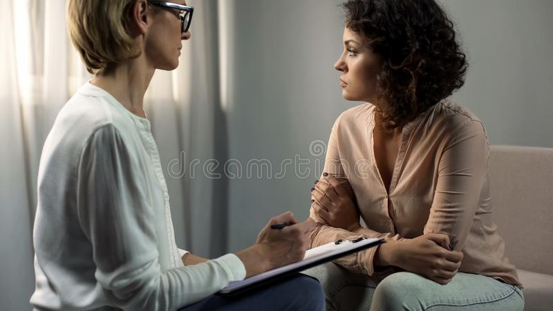 Lyssnande deprimerad dampatient för yrkesmässig psykolog, upplösningsterapi royaltyfri fotografi
