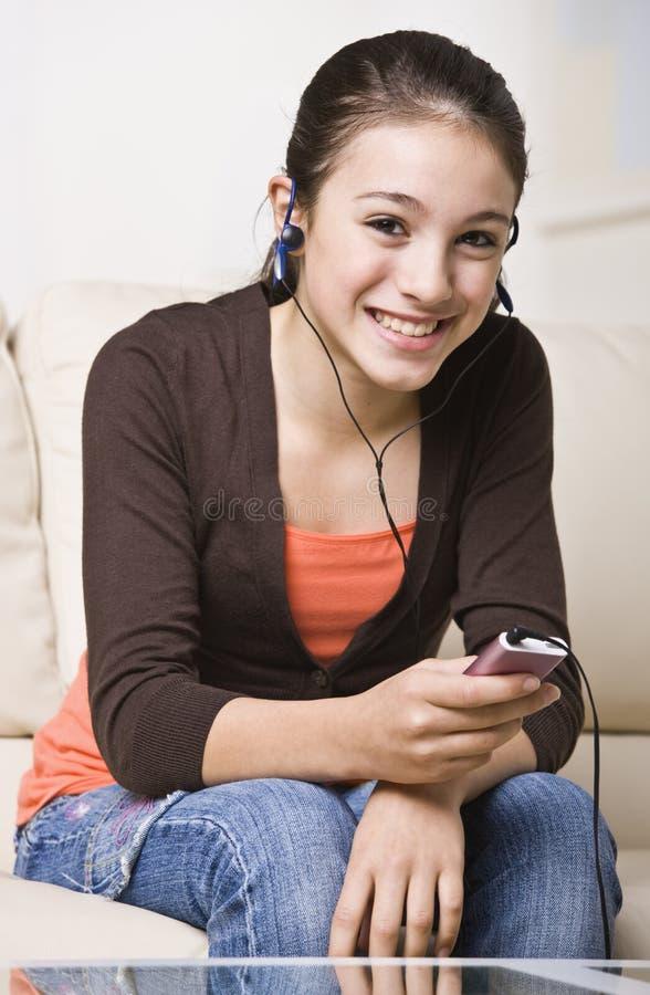 lyssnande le för musik som är teen till royaltyfria foton
