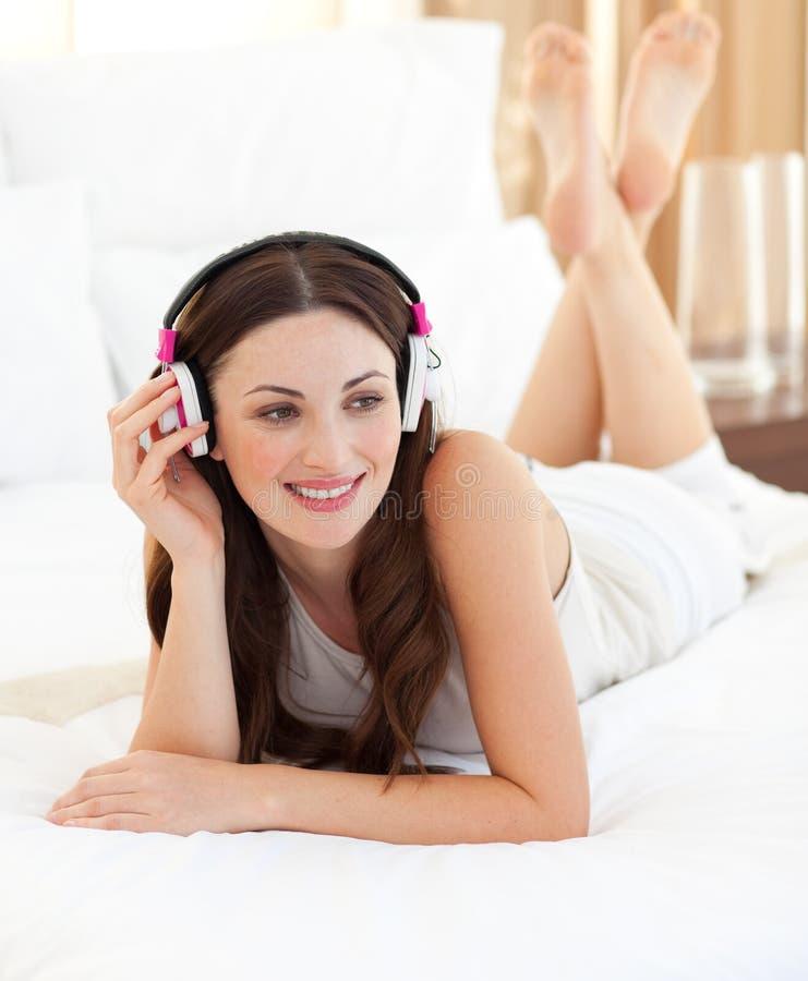 lyssnande liggande musikkvinna för attraktivt underlag royaltyfri bild