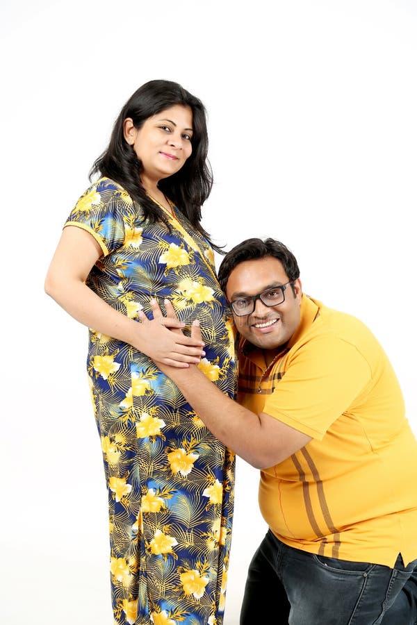 Lyssnande ljud för ung make från hans gravida buk för wife's arkivbilder