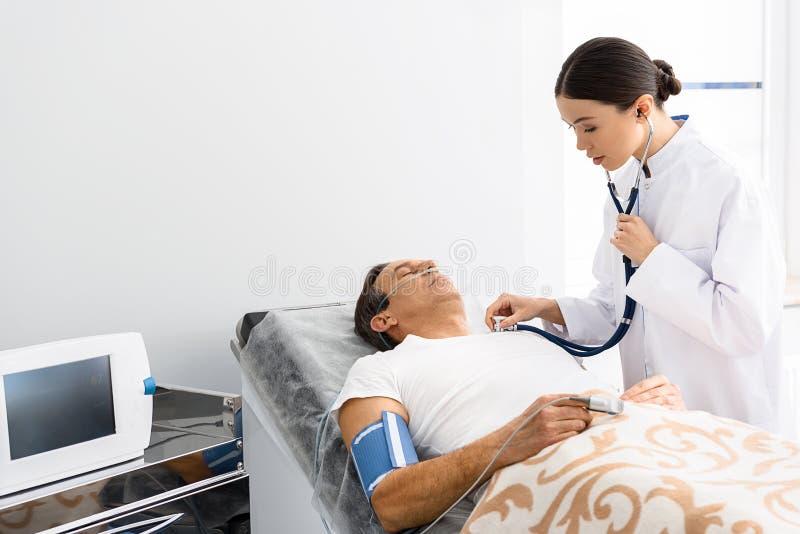 Lyssnande man för lugna kvinnlig doktor vid stetoskopet arkivfoto
