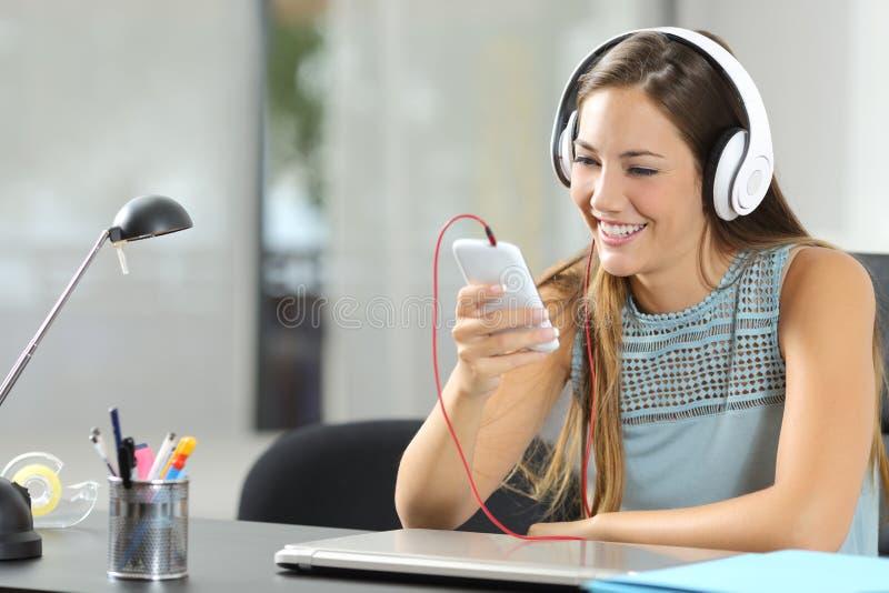 Lyssnande musik för flicka med smartphonen och hörlurar royaltyfri fotografi