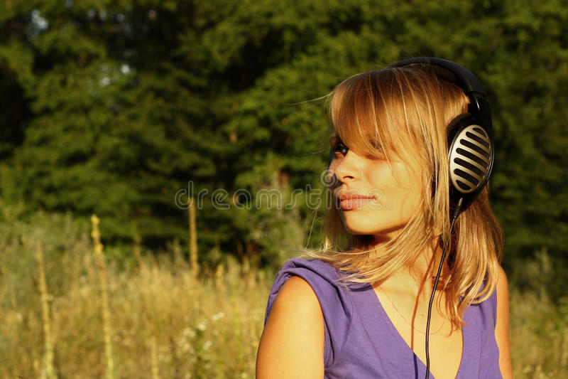 lyssnande musik för flicka utomhus till att gå arkivfoto