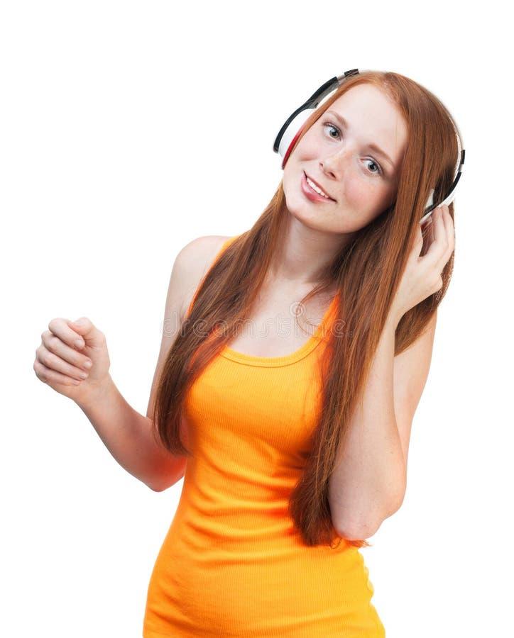 lyssnande musik för flickahörlurar Isolerat på vit backgroun arkivbilder