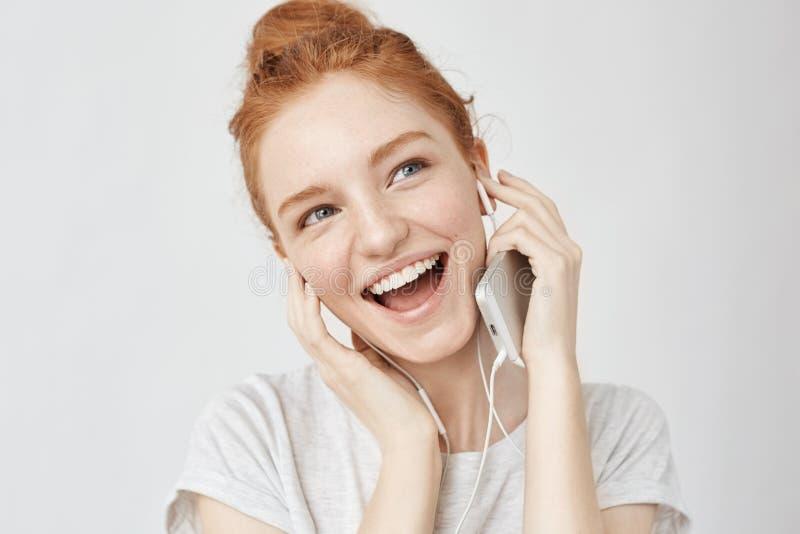 Lyssnande musik för gladlynt rävaktig flickafröjd, i att le för hörlurar royaltyfri bild