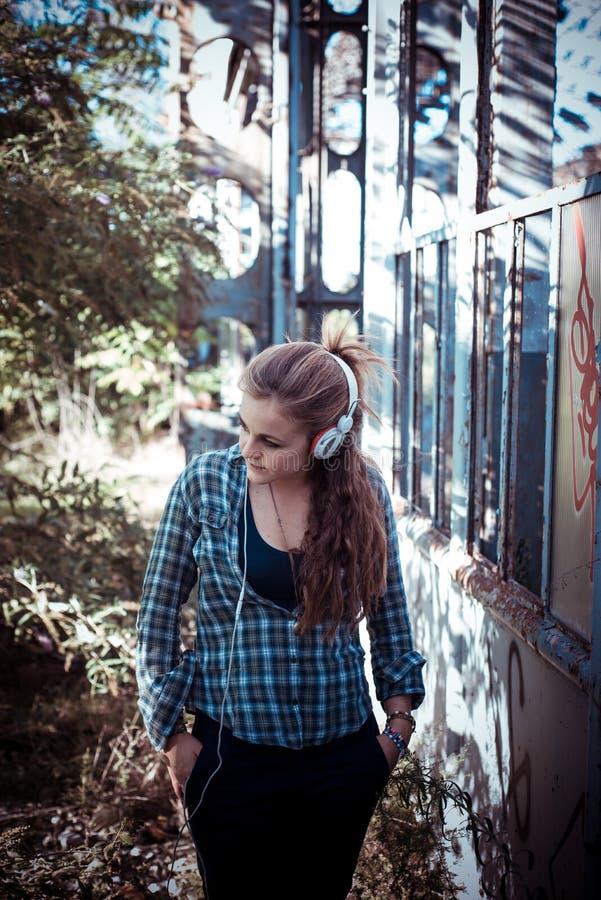 Lyssnande musik för härlig ung blond hipsterkvinna royaltyfri foto