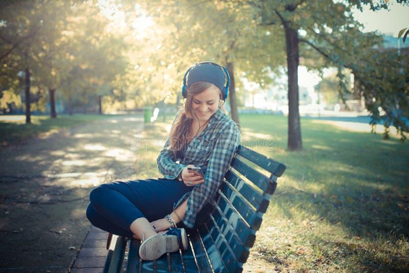 Lyssnande musik för härlig ung blond hipsterkvinna royaltyfria bilder