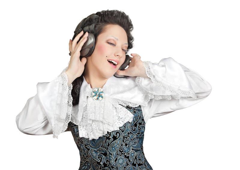 lyssnande musik för hörlurar som ler till kvinnan arkivfoto