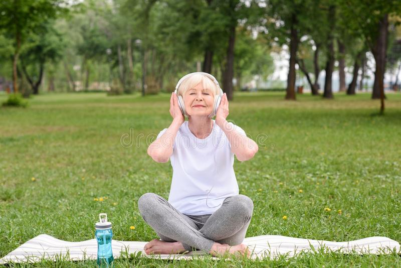 lyssnande musik för lycklig äldre kvinna med hörlurar, medan sitta på yoga som är matt med flaskan av vatten arkivbilder