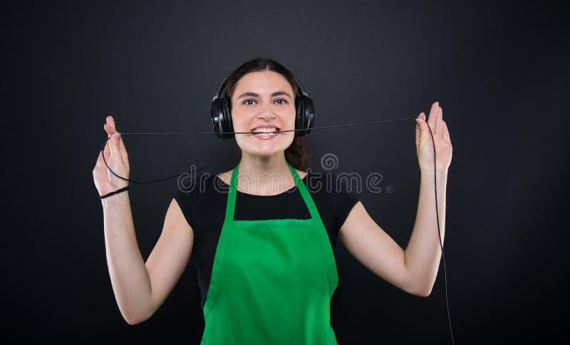 Lyssnande musik för lycklig flickasäljare från hennes hörlurar fotografering för bildbyråer