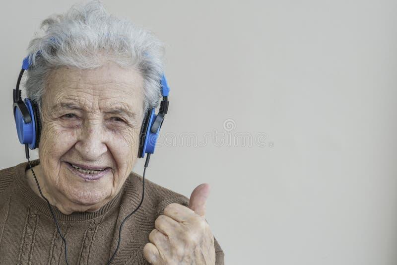 Lyssnande musik för lycklig hög kvinna med hörlurar royaltyfria bilder