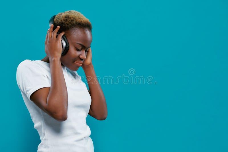 Lyssnande musik för nätt afrikansk flicka med hörlurar royaltyfri bild
