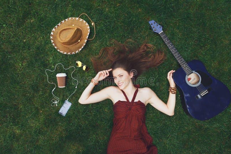 Lyssnande musik för nätt ung flicka i hörlurar som ligger på gräs arkivbild