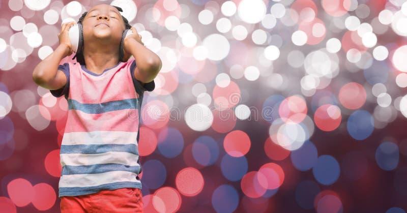 Lyssnande musik för pojke till och med hörlurar över glödande bokeh arkivfoto