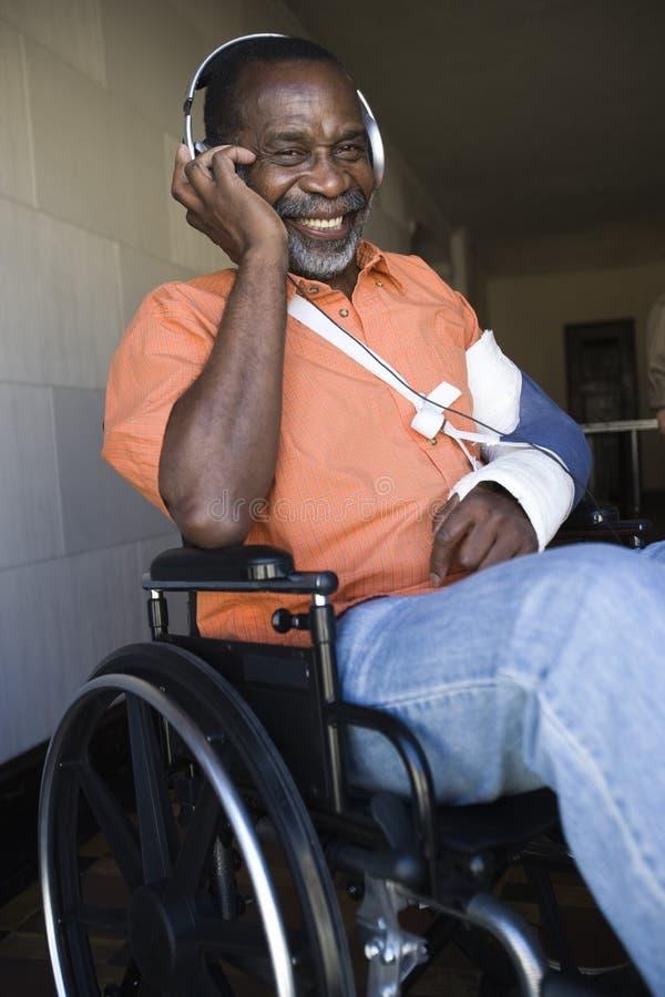 Lyssnande musik för sårad man, medan sitta på rullstolen royaltyfri fotografi