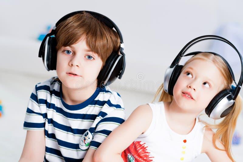 Lyssnande musik för syskongrupp med hörlurar fotografering för bildbyråer