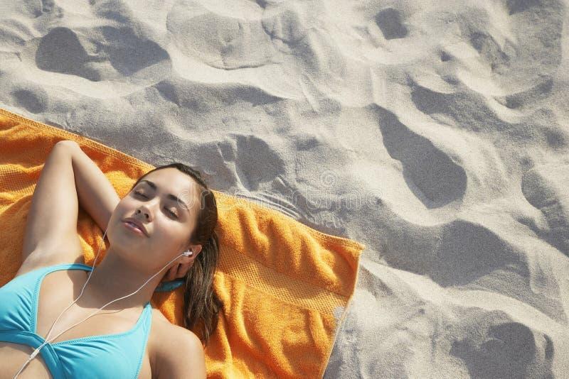 Lyssnande musik för tonårs- flicka, medan ligga på strandhandduken royaltyfri foto