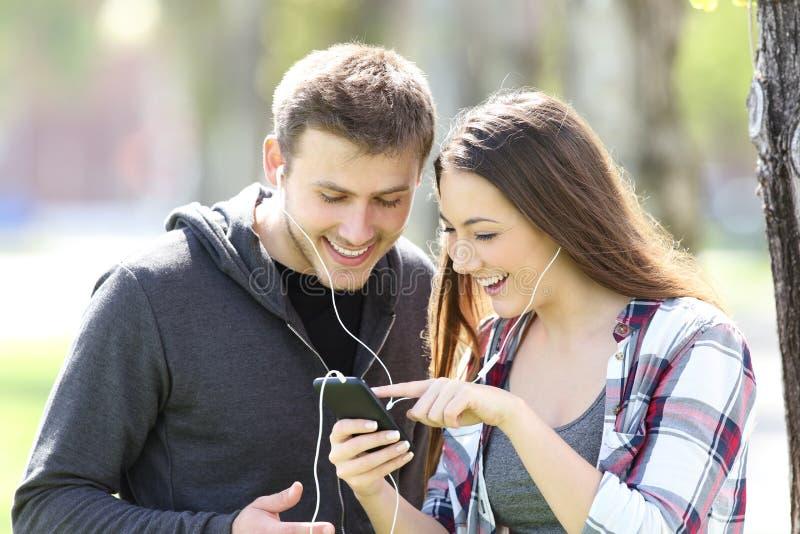 Lyssnande musik för två vänner och väljasång royaltyfri bild