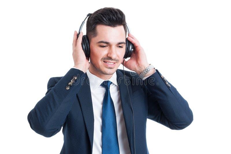 Lyssnande musik för ung affärsman på hörlurar som ser lycklig arkivbild