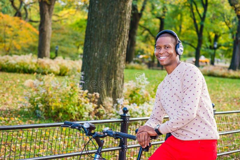 Lyssnande musik för ung afrikansk amerikanman i Central Park som är ny fotografering för bildbyråer