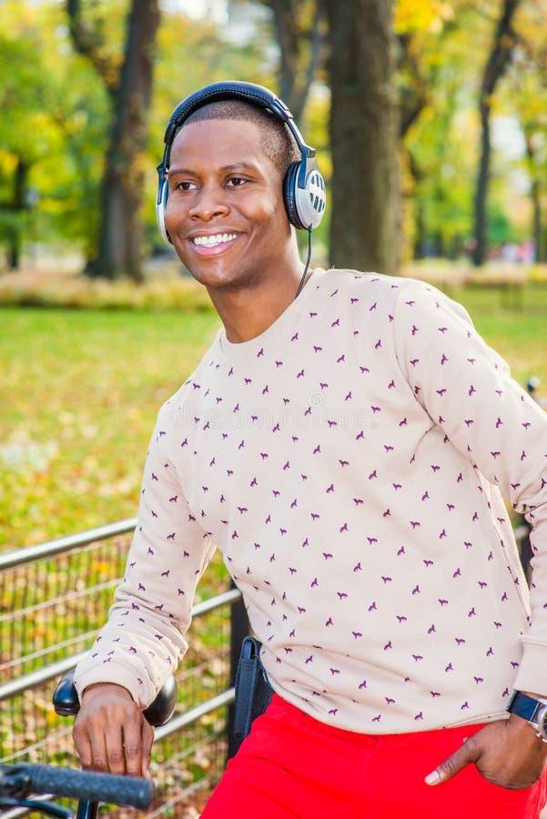 Lyssnande musik för ung afrikansk amerikanman i Central Park som är ny arkivbilder
