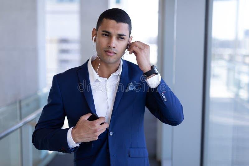 Lyssnande musik för ung blandad-lopp affärsman på mobiltelefonen i modernt kontor royaltyfria foton