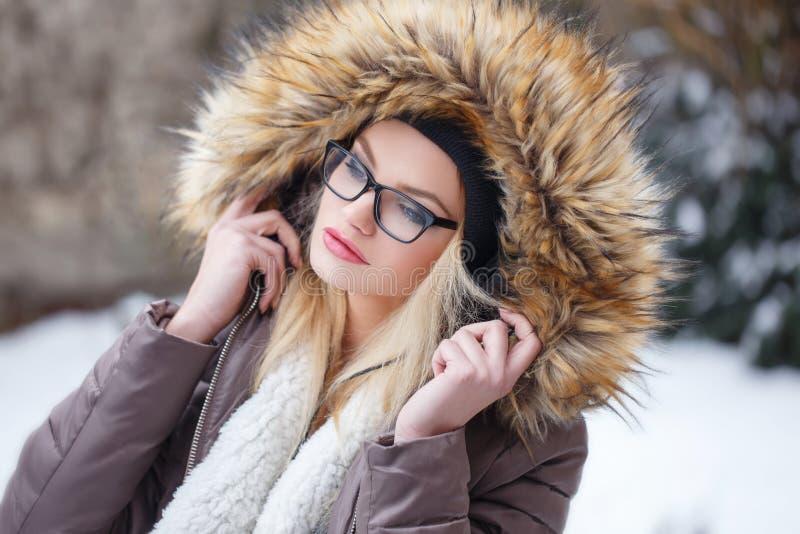 Lyssnande musik för ung blond kvinna på vintern arkivfoto