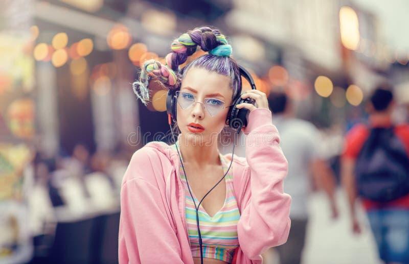 Lyssnande musik för ung frireligiös flicka i hörlurar på de fullsatta gatorna Suddig stads- bakgrund Avantgardemode arkivbild