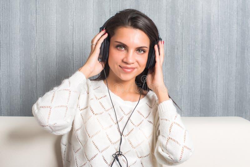 Lyssnande musik för ung kvinna med hörlurar i rum hemma på soffablicken på kameran royaltyfria bilder