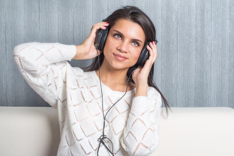 Lyssnande musik för ung kvinna med hörlurar i rum hemma på soffan arkivbild
