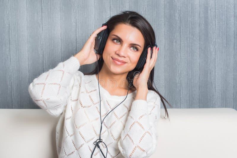 Lyssnande musik för ung kvinna med hörlurar i rum hemma på soffan arkivbilder